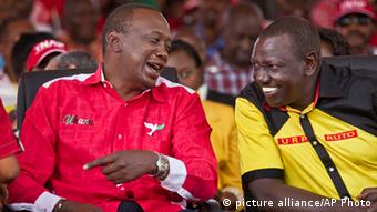 Kenyan President Uhuru Kenyatta and his deputy William Ruto chat during a political campaign event.