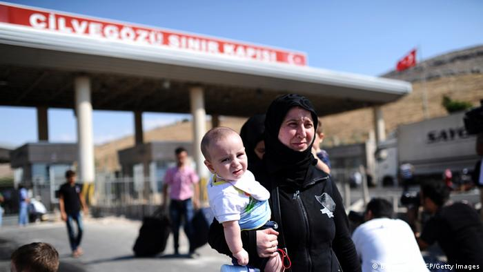 A woman of Middle-Eastern descent wearing a black headscarf and robes carries a small child through an outdoor customs gate (Photo: Bulent Kilic)