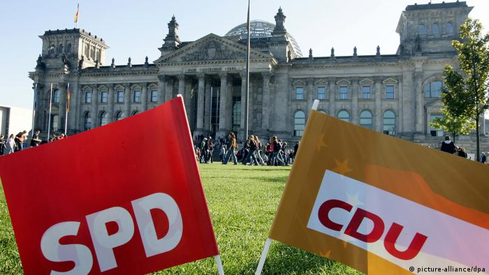 CDU and SPD flags in front of the German house of parliament Photo: Gero Breloer dpa