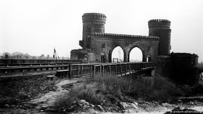 A black and white image of the two remaining towers of the Ludendorff Bridge.