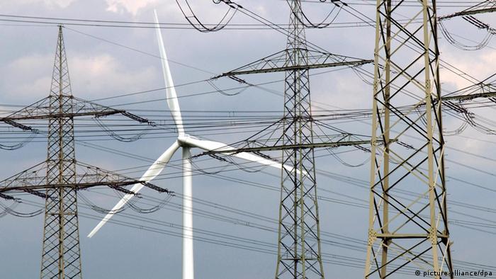 Ein Windkraftrad steht in Niederaußem zwischen Strommasten ; Foto: Horst Ossinger dpa/lnw +++(c) dpa - Report+++