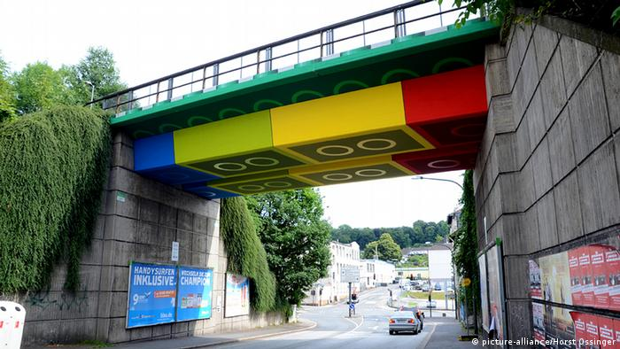 A cement railway bridge painted with a lego brick design.