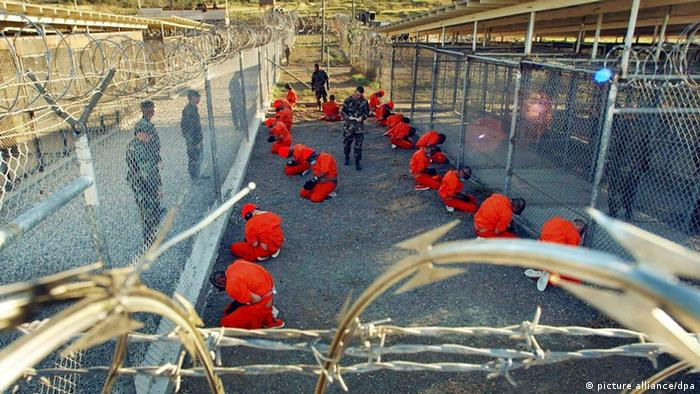 Inmates sit on the ground surrounded by fences and guards at Guantanamo