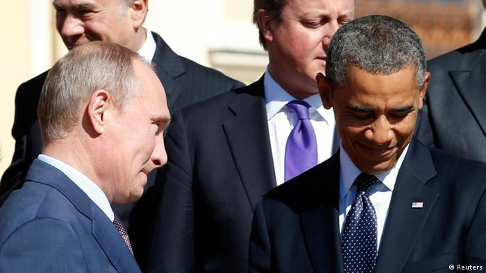Russian President Vladimir Putin (L) walks past U.S. President Barack Obama (R) during a group photo at the G20 Summit in St. Petersburg September 6, 2013. REUTERS/Kevin Lamarque