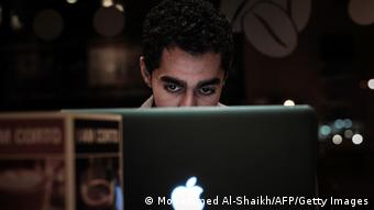 A man peers over the top of his computer screen