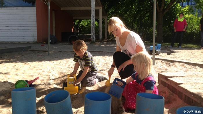 Dahlia-Sophie Mayer spielt mit Kindern einer Kindertagesstätte im Sand.