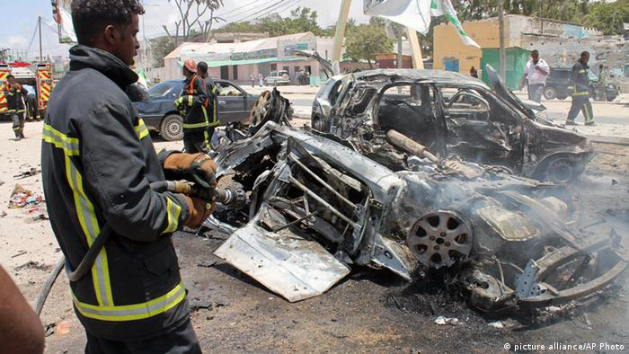 A firefighter sprays water on destroyed cars in Mogadishu, Somalia, Saturday, Sept, 7, 2013. Police in Somalia say two explosions against a restaurant frequented by government workers has killed at least 15 people. Early reports indicated that a car bomb blast and a suicide bomber attacked a restaurant near Mogadishu's State House. The restaurant, The Village, has been attacked by militants before. (Farah Abdi Warsameh)
