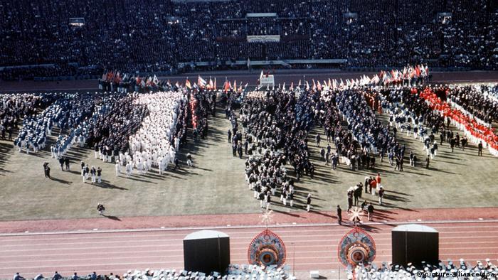 Der Einmarsch der Nationen ins Nationalstadion von Tokio bei der feierlichen Eröffnung der XVIII. Olympischen Sommerspiele am 10.10.1964 nähert sich seinem Abschluss, der Innenraum der mit Zuschauern dicht besetzten Sportstätte hat sich mit den Mannschaften der teilnehmenden Länder gefüllt. (Foto: dpa)