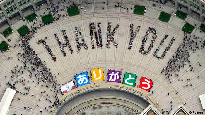 An aerial view shows people sitting in formation to the words thank you and displaying signs that collectively read Arigato (Thank You) during an event celebrating Tokyo being chosen to host the 2020 Olympic Games, at Tokyo Metropolitan Government Building in Tokyo, in this photo taken by Kyodo September 8, 2013 (Photo: REUTERS/Kyodo)