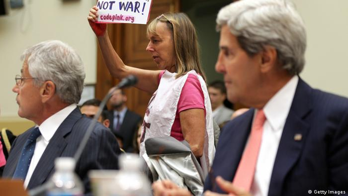 WASHINGTON, DC - SEPTEMBER 04: Medea Benjamin (C) of CodePink protests as U.S. Secretary of State John Kerry (R) and Defense Secretary Chuck Hagel testify during a hearing on Syria: Weighing the Obama Administration's Response before the House Foreign Affairs Committee September 4, 2013 on Capitol Hill in Washington, DC. Meanwhile, the Senate Foreign Relations Committee is considering a resolution drafted by committee chairman Sen. Robert Menendez (D-NJ) and ranking member Sen. Bob Corker (R-TN) to authorize military against the Bashar al-Assad regime that can be voted on as early as today. (Photo by Alex Wong/Getty Images)