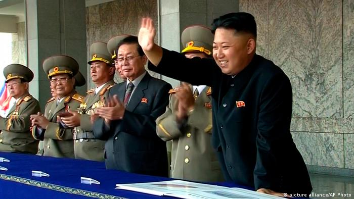 In this image taken from video North Korean leader Kim Jong Un, right, smiles as he waves to spectators and participants of a military parade celebrating the 65th anniversary of the country's founding (Photo: AP Photo/KRT via AP Video)