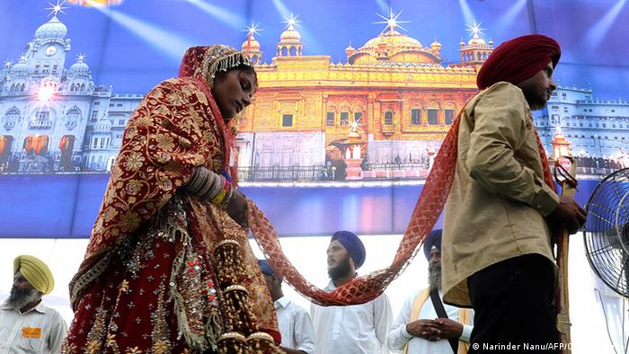 An Indian bride and groom walk past a poster of the Golden Temple during a mass marriage ceremony for some 121 low-income couples from the India-Pakistan border area on the outskirts of Amritsar on September 16, 2010. (Photo: AFP)