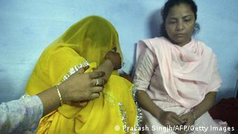 The hand of an unidentified relative (L) reaches to comfort Farzana (C) as her sister Saira Bano (R) sits next to her in New Delhi, 18 May 2003. (Photo: AFP)