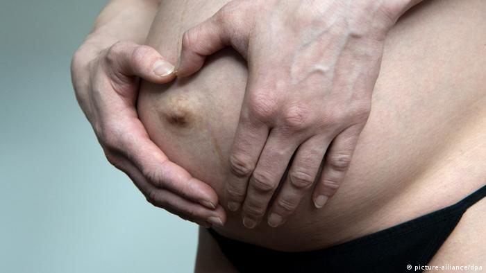 Pregnant woman holding her belly with her navel showing