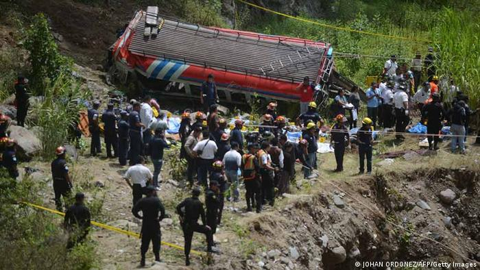 Members of the public prosecutor's office and rescuers work on the site of a bus accident on September 9, 2013 in the municipality of San Martin Jilotepeque, Chimaltenango Departament, about 65 km west Guatemala City. A bus carrying scores of passengers plunged down a steep cliff in western Guatemala killing at least 43 people and injuring 40 others, firefighters said. AFP PHOTO / Johan ORDONEZ (Photo credit should read JOHAN ORDONEZ/AFP/Getty Images)