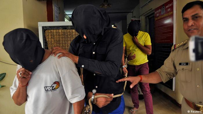 Police escort men (face covered) accused of a gang rape, outside a police station on the outskirts of New Delhi in August 2013.