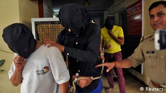 Police escort men (face covered) accused of a gang rape, outside a police station in Noida on the outskirts of New Delhi August 31, 2013. (Photo: Reuters)