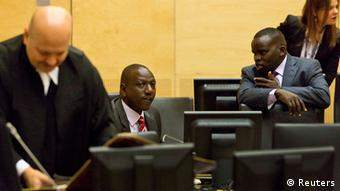 Kenya's Deputy President William Ruto speaks with broadcaster Joshua arap Sang (R) in the courtroom before their trial at the International Criminal Court (ICC) in The Hague September 10, 2013. Ruto appeared at the International Criminal Court on Tuesday for the opening of his trial on charges of co-orchestrating a post-election bloodbath five years ago. Ruto and his co-accused, the broadcaster Joshua arap Sang, could face long prison terms if convicted. To the left is defense counsel Karim Khan. REUTERS/Michael Kooren (NETHERLANDS - Tags: CIVIL UNREST POLITICS CRIME LAW)