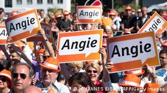 Supporters of German Chancellor Angela Merkel and head of German Christian Democratic Union CDU hold electoral placards reading 'Angie' during her visit ahead of the upcoming September 22 legislative elections, on September 7, 2013 in Oranienburg. AFP PHOTO / JOHANNES EISELE (Photo credit should read JOHANNES EISELE/AFP/Getty Images)