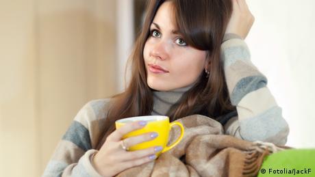 Symbolbild Frau nachdenklich Tasse Tee Kaffee Wolldecke Decke Sofa Couch