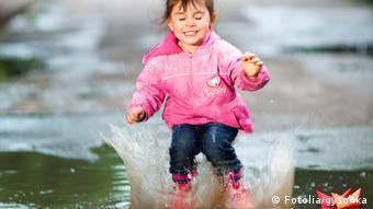 Ein kleines Mädchen in Regenjacke und Gummistiefeln hüpft fröhlich in eine Pfütze.