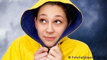 Eine Frau in einer Regenjacke. Im Hintergrund dunkle Regenwolken.