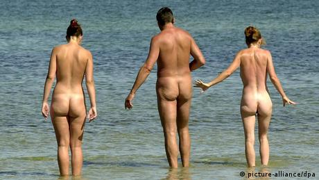 Three naked people seen from behind