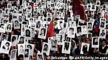Activists of the Chilean Human Rights organization 'Detained and Disappeared People' take part in a demonstration in Santiago on September 8, 2013, in remembrance of late President (1970-1973) Salvador Allende, who died on September 11, 1973 during the military coup d'etat led by general Augusto Pinochet. On September 11 Chile will commemorate the 40th anniversary of the coup that toppled Salvador Allende and brought dictator Pinochet to power. AFP PHOTO/Sebastian Silva (Photo credit should read Sebastian Silva/AFP/Getty Images)