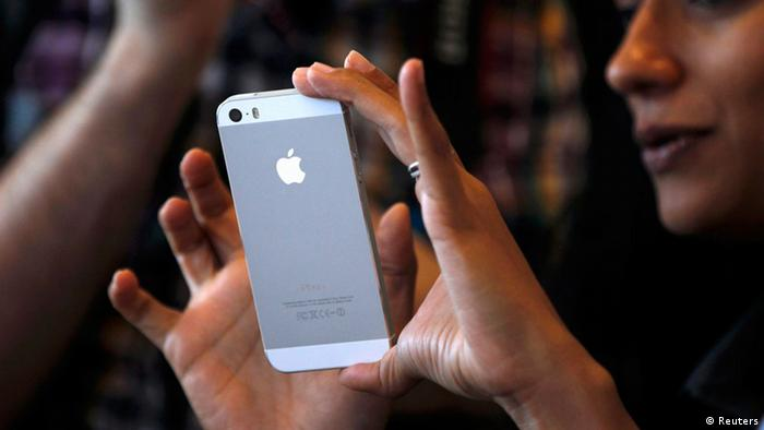 A woman tries the silver colored version of the new iPhone 5S after Apple Inc's media event in Cupertino, California September 10, 2013. REUTERS/Stephen Lam (UNITED STATES - Tags: BUSINESS SCIENCE TECHNOLOGY BUSINESS TELECOMS)