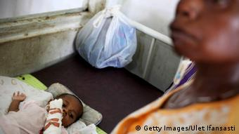 A baby lies sick with malaria in Indonesia