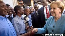 Bundeskanzlerin Angela Merkel (CDU) wird am Dienstag (12.07.2011) in Nairobi in Kenia von Studenten an der Universtät Nairobi begrüßt. Merkel ist zu politischen Gesprächen in Kenia und hält eine Rede an der Universität in Nairobi. Am Abend reist Merkel weiter nach Angola und Nigeria. . Foto: Michael Kappeler dpa/lbn