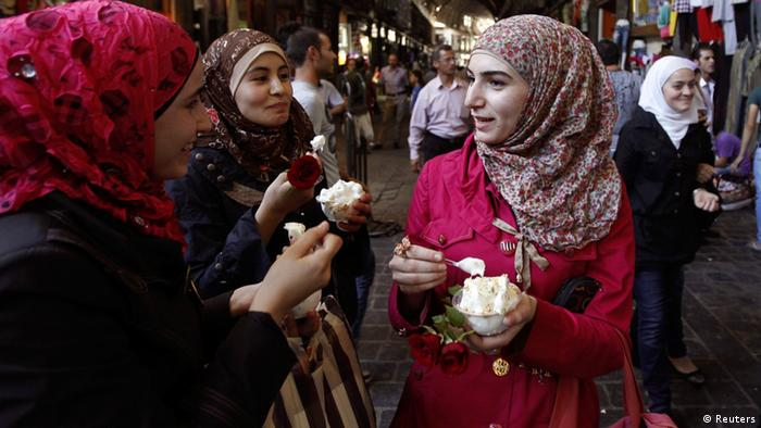 Syrian women eat ice cream at the Al-Hamidieh market in old Damascus, September 8, 2013. REUTERS/Khaled al-Hariri (SYRIA - Tags: POLITICS CONFLICT CIVIL UNREST SOCIETY FOOD)
