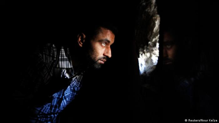 Ein Kämpfer der syrischen Freien Syrien Armee blickt durch ein Loch in einer Mauer - in seiner Umgebung ist es dunkel (Foto: REUTERS/Nour Kelze)
