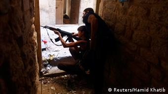 Ahmad Abu Layl, a 15 year-old fighter from the Free Syrian Army, aims his weapon as his father stands behind him in Aleppo September 10, 2013. REUTERS/Hamid Khatib (SYRIA - Tags: POLITICS CIVIL UNREST CONFLICT MILITARY)