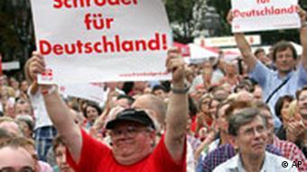 Bildergalerie Wahl05 Besucher zeigen am Samstag, 10. Sept. 2005, waehrend einer Wahlkampfveranstaltung der SPD in Bonn mit Bundeskanzler Gerhard Schroeder Schilder