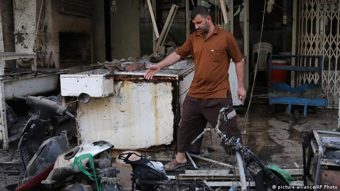 A man inspects the site of a double bomb attack on a Shiite mosque in Kasra neighborhood in northern Baghdad, Iraq, Thursday, Sept. 12, 2013. A suicide attacker staged a double bombing near a Shiite mosque in northern Baghdad as worshippers were leaving after evening prayers on Wednesday, according to Iraqi authorities. (AP Photo/Khalid Mohammed)
