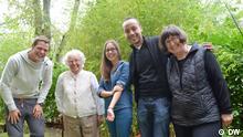 Jonas, Kristina, Nasser und zwei Bewohner des Mehrgenerationenwohnhauses lächeln in die Kamera.