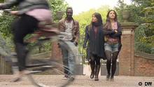 Eric, Nichole und Almudena überqueren eine Straße. Vorne links ist verschwommen eine Hinterrad eines Fahrrads und die Beine der Fahrerin zu sehen.