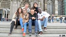 Die sechs Kandidaten sitzen auf Treppenstufen vor dem Kölner Dom und lächeln in die Kamera.