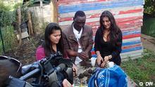 Almudena, Nichole und Eric stehen an einem Tisch und stellen Samenkugeln her.