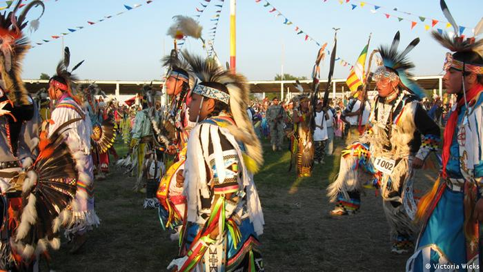 At the Crow Creek Tribe powwow dancers perform in colorful, bright and fancy costumes decorated with feathers