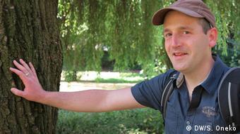 Teacher Thomas Knechten leans against a tree