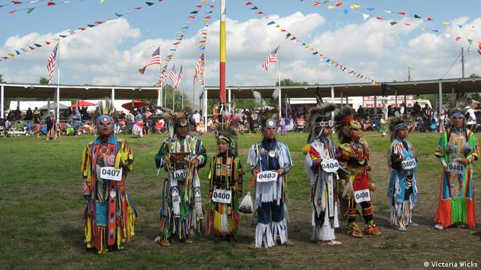 Young contestants in tribal costume line up after dancing at the powwow
