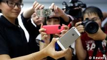 Journalists take photos of a new iPhone 5S during Apple Inc's announcement event in Beijing, September 11, 2013. Apple Inc's millions of Chinese fans will celebrate the near-simultaneous launch of the latest iPhone in China and the United States, but one group will have little to cheer - the smugglers. An early launch of Apple's latest smartphone in China is expected to stifle a thriving grey market worth billions of dollars a year built around smuggling from Hong Kong, where in the past the U.S. tech giant's gadgets have gone on sale months before they reach official channels in the mainland. REUTERS/Jason Lee (CHINA - Tags: MEDIA BUSINESS SCIENCE TECHNOLOGY)