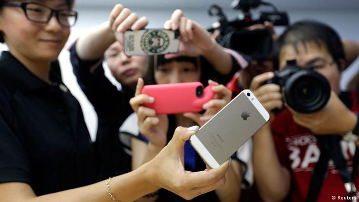 Journalists take photos of a new iPhone 5S during Apple Inc's announcement event in Beijing (Jason Lee/REUTERS)