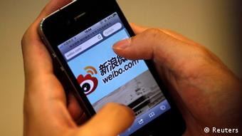 A man holds an iPhone as he visits Sina's Weibo microblogging site in Shanghai in this May 29, 2012 file photo. Sina Corp, one of China's biggest Internet firms, runs the microblogging site, which has 500 million registered users. It also employs the censors. The Sina Weibo censors are a small part of the tens of thousands of censors employed in China to control content in traditional media and on the Internet. Picture taken May 29, 2012. REUTERS/Carlos Barria/Files (CHINAMEDIA - Tags: MEDIA BUSINESS TELECOMS)