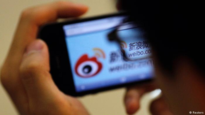 A man holds an iPhone as he visits Sina's Weibo microblogging site in Shanghai in this May 29, 2012 file photo. Sina Corp, one of China's biggest Internet firms, runs the microblogging site, which has 500 million registered users. It also employs the censors. The Sina Weibo censors are a small part of the tens of thousands of censors employed in China to control content in traditional media and on the Internet. Picture taken May 29, 2012. REUTERS/Carlos Barria/Files (CHINA - Tags: POLITICS SCIENCE TECHNOLOGY BUSINESS TELECOMS)