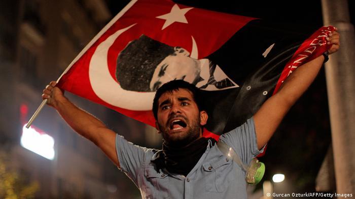 A man waves a Turkish flag showing the founder of modern Turkey, Kemal Atatürk