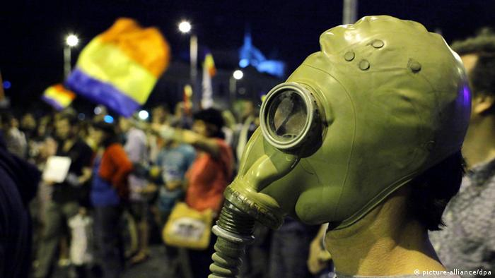 A Romanian protestor, wearing an old military gas mask, stands after his fellow activists were occupying University Plaza during a demonstration, in Bucharest, Romania, against the opening of the Rosia Montana open cast gold mine, 08 September 2013. Romania's government has approved a draft law enabling Canada's Gabriel Resources to open the mine.Thousands of protestors marched to the Romanian government headquarters during an unauthorized demonstration, occupying the University Plaza in downtown Bucharest. EPA/ROBERT GHEMENT