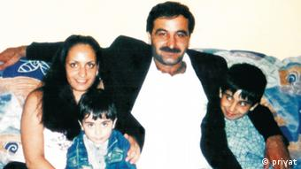 A father and his three children - all of Turkish descent - smile happily at the camera in a domestic setting.
